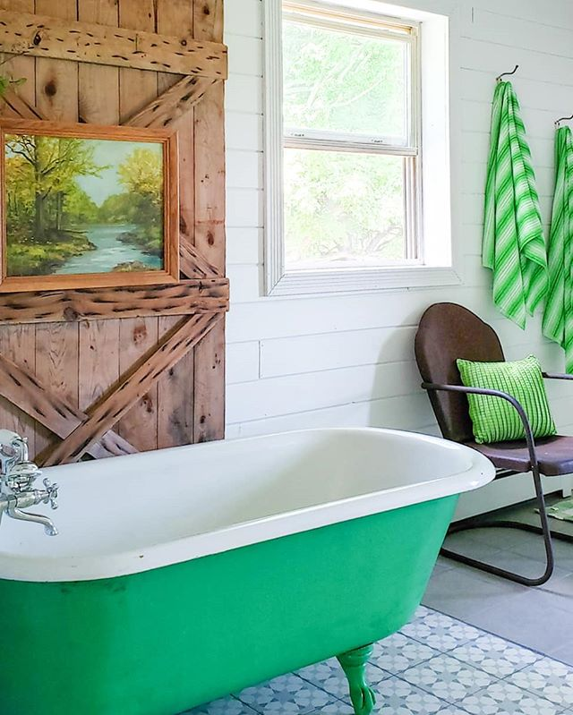Modern rustic bathroom with green bathtub